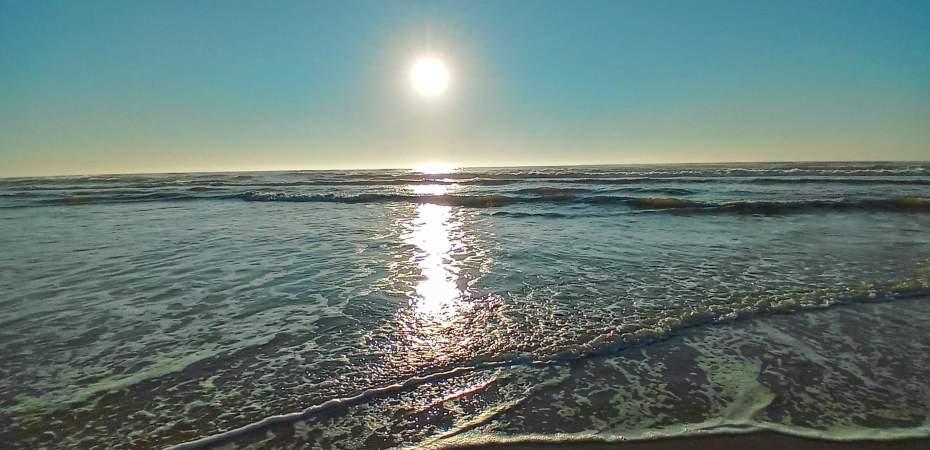 Nascer do sol na praia. Céu azul.